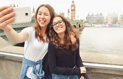 Gelukkige glimlachende mooie tieners die selfie in Big Ben, Londen nemen royalty-vrije stock afbeelding