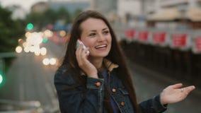 Gelukkige, glimlachende mooie vrouw die op de telefoon spreken die zich op de brug bevinden en De wind blaast haar haar 4K stock video