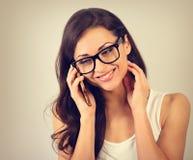 Gelukkige glimlachende mooie vrouw in oogglazen die op mobiele ph spreken stock afbeeldingen