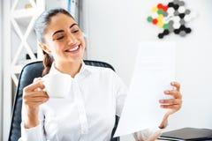 Gelukkige glimlachende onderneemster die documenten analyseren terwijl het hebben van koffiepauze Stock Fotografie