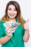 Gelukkige glimlachende onderneemster die in groen jasje met duimen op gebaar en geld dragen Het super gelukkige opgewekte succes  stock afbeelding