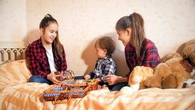 Gelukkige glimlachende oudere meisjes die op bed met peuterjongen spelen stock foto's