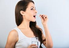 Gelukkige glimlachende positieve vrouw die de pil eten en het glas water in de hand op blauwe achtergrond houden close-up royalty-vrije stock afbeeldingen