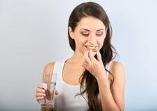 Gelukkige glimlachende positieve vrouw die de pil eten en het glas water in de hand op blauwe achtergrond houden close-up stock afbeelding