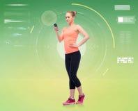 Gelukkige glimlachende sportieve jonge vrouw met smartphone stock afbeelding
