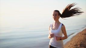 Gelukkige glimlachende sportvrouw die op het zandstrand dichtbij het overzees lopen stock videobeelden