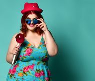 Gelukkige glimlachende te zware vette mollige vrouw in grappige hoed en zonnebril met extra grote lolly op populaire munt royalty-vrije stock fotografie