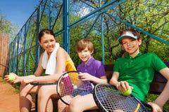 Gelukkige glimlachende tennisspelers die rust na reeks hebben Stock Foto