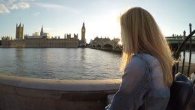 Gelukkige glimlachende tiener vrouwelijke toerist die op de brug van Westminster het parlement en Big Ben in Londen bewonderen - stock videobeelden