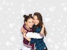 Gelukkige glimlachende tieners die over sneeuw koesteren Royalty-vrije Stock Foto's