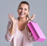 Gelukkige glimlachende verrassingsvrouw met roze het winkelen zak stock foto's