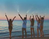 Gelukkige glimlachende vrienden bij het strand met fonkelende kaarsen Royalty-vrije Stock Foto