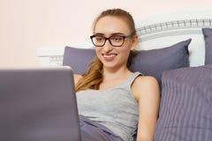 Gelukkige glimlachende vrouw die in glazen het bed voor haar laptop in de ochtendslaapkamer liggen royalty-vrije stock afbeeldingen