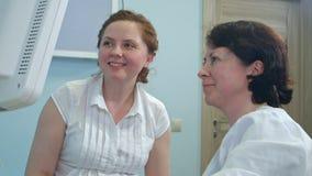 Gelukkige glimlachende vrouw die haar toekomstige baby op de echoscopie bekijken Stock Foto's