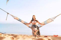 Gelukkige glimlachende vrouw die in hangmat scharnierend tussen palmen aan de overzeese kant slingeren royalty-vrije stock foto's