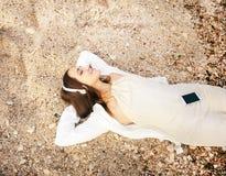 Gelukkige glimlachende vrouw die op een overzeese zand en het luisteren muziek liggen stock foto's