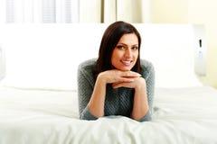 Gelukkige glimlachende vrouw die op middelbare leeftijd op het bed liggen stock fotografie