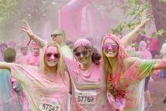 Gelukkige glimlachende vrouw drie omvat met roze kleurenpoeder Stock Afbeeldingen