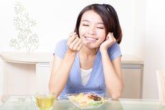Gelukkige glimlachende vrouw met salade thuis Royalty-vrije Stock Foto's