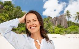 Gelukkige glimlachende vrouw op de zomerstrand stock fotografie