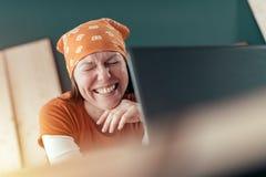 Gelukkige glimlachende vrouwelijke timmerman tijdens online praatje stock foto