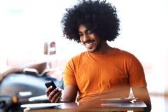 Gelukkige glimlachende zwarte mens die mobiele telefoon bekijken Stock Afbeeldingen