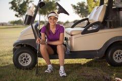 Gelukkige golfspelerzitting in een golfkar Royalty-vrije Stock Afbeeldingen
