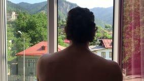 Gelukkige grappige dansende mens die aan balkon met prachtige mening, het openen gordijnen in de ochtend, nieuwe dag uitgaan stock videobeelden