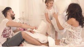 Gelukkige grappige familie die een hoofdkussenstrijd in bed hebben stock video
