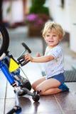 Gelukkige grappige peuterjongen die van twee jaar zijn eerste fiets herstellen Stock Foto's
