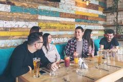 Gelukkige groep beste vrienden die pret het drinken bier hebben terwijl het wachten van voedselorde bij restaurant stock afbeelding
