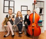Gelukkige groep die jonge geitjes muzikale instrumenten spelen Stock Afbeeldingen