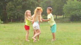 Gelukkige groep kleine vrienden die samen in openlucht in de zomer spelen stock footage