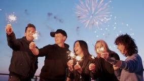 Gelukkige groep vrienden bij betoverende partij met vuurwerk op de achtergrond en verlichtingssterretjes in handen, die pret hebb stock video
