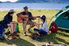 Gelukkige groeps jonge vrienden in kamperende tentpartij die speelm hebben royalty-vrije stock foto
