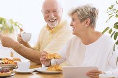 Gelukkige grootmoeder die ontbijt eten stock afbeelding