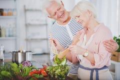 Gelukkige grootmoeder die salade mengen stock foto