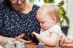 Gelukkige grootmoeder en leuke kleindochter die smartphone, het onderwijzen gebruiken royalty-vrije stock afbeeldingen