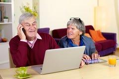 Gelukkige grootvader die op de telefoon met zoon thuis spreken Stock Foto