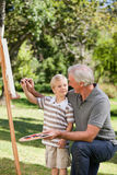 Gelukkige Grootvader en zijn kleinzoon het schilderen Stock Afbeeldingen