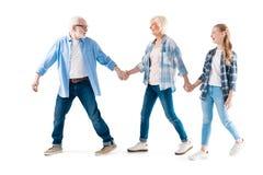 Gelukkige grootvader, grootmoeder en kleindochter die en handen samen lopen houden stock foto's