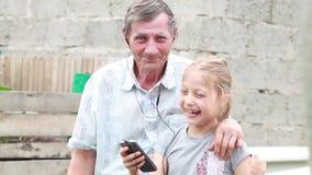 Gelukkige grootvader met kleindochter koesteren die in de werf lachen stock video