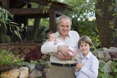 Gelukkige grootvader met zijn kleinkinderen in de tuin Stock Foto