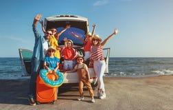 Gelukkige grote familie in reis van de de zomer de autoreis door auto op strand stock afbeelding