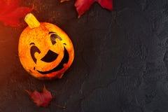 Gelukkige Halloween-vakantieachtergrond met grappige pompoen en de herfstbladeren Stock Afbeeldingen