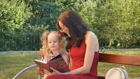 Gelukkige het Boekzitting van de Familielezing op de Bank in het Park Jonge Moeder die Oogglazen en Rode Kleding, weinig dragen stock footage