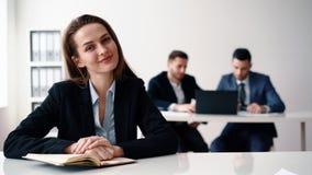 Gelukkige het glimlachen bedrijfsvrouwenzitting in bureau met haar commercieel team stock videobeelden