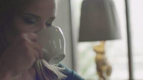 Gelukkige het glimlachen vrouw het drinken kop van koffie in koffie stock footage