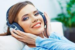 Gelukkige het glimlachen vrouw het luisteren muziek met hoofdtelefoons Stock Foto