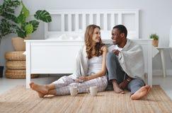 Gelukkige het houden van paar het drinken cacao op de winterochtend in bed royalty-vrije stock afbeelding